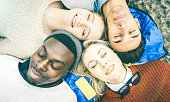 Top view of multiracial best friends having fun resting together outdoors on sunny day - Happy friendship and peace concept with young multicultural people on relax mood - Bright vintage filtered look