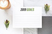Top view of new year 2019 goals on white paper card and coffee cup on marble table office desk.resolutions for life