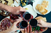 Top view of people eating and toasting with glasses of red wine. Friends or family different ages enjoying dinner concept. Delicious snack on party or picnic time. Italian style banquet.