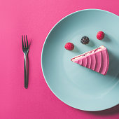 top view of piece of pink cake with berries on plate on pink surface