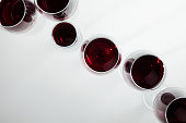top view of red wine in glasses arranged isolated on white