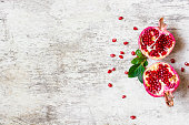 ripe pomegranate divided into two pieces with seeds on white wooden background with copy space. top view