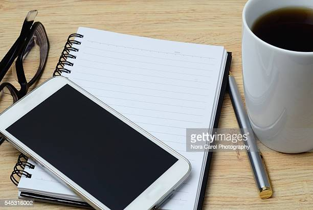 Top view of smart phone, notepad, spectaclesand pen