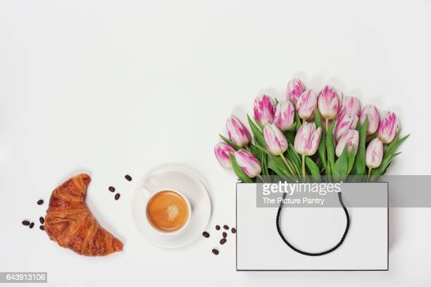 Top view of spring flowers, coffee and croissant. Flat lay image. Holiday, romance of modern life concept