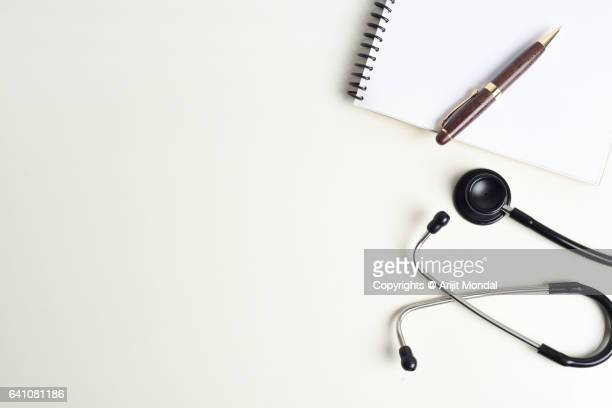 Top View Of Stethoscope And Writing Pad On White Desk In Doctors Office