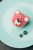 top view of sweet pink muffin in shape of bear and fresh blueberries on blue plate
