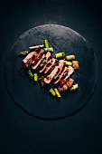 top view of tasty sliced grilled meat with asparagus on black slate board