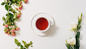 Herbal tea. Top view of a cup filled with herbal tea standing in the middle of the white desk while being surrounded by beautiful flowers