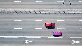 Aerial view of the red and pink cars passing along the road on a sunny day. Kiev, Ukraine. Drone photography