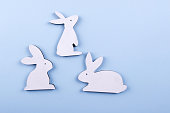 Top view  of three white wooden bunny on blue pastel background. Copy space