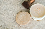 top view of translucent powder with brush and puff to make up for women beauty