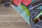 Top view of travel accessories for a mountain trip on old wooden background : hiking boots, pants, camera, bottle, rope, and map.