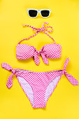 Top view of two pieces pink chequered swimming suit and white sunglasses over yellow background.