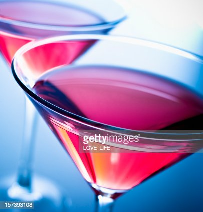 Top view of two pink cosmopolitan drinks on blue background