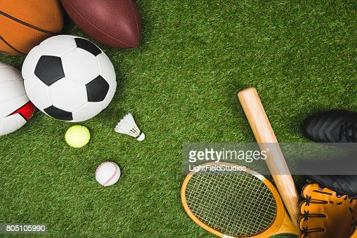 top view of various sport balls, baseball bat and glove, badminton racket on green lawn : Stock Photo