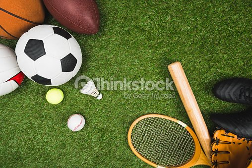 Top view of various sport balls, baseball bat and glove, badminton racket on green lawn