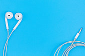 Top view of White Earphones on Blue background. Copy space. Music is my life concept