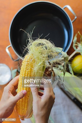 top view of woman prepares corn for cooking in bowl : Stock Photo
