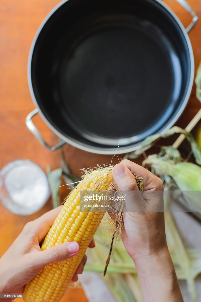 top view of woman prepares corn for cooking in bowl : ストックフォト