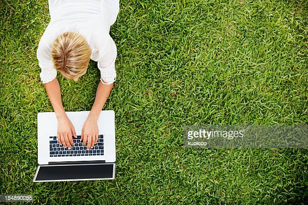 Top view of young girl lying on grass and working