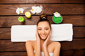 Top view of nice young woman laying in spa salon relaxing touching face