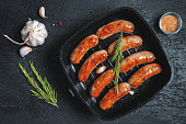 Top view on fried sausages in a black frying pan on a black stone table with garlic and greens