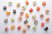 Top view on classic sushi rolls pattern. Asian food restaurant delivery, platter set on white background