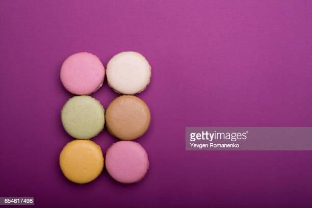 Top view on macaron or macaroon dessert on purple background