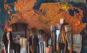 Top view picture of wooden paintbrush set different size with old palette on the background