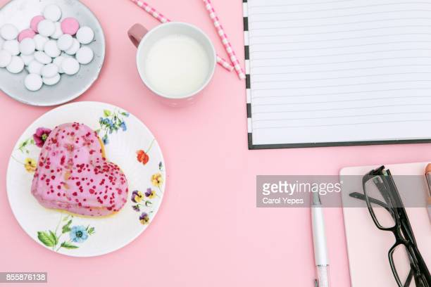 top view pink notebook, beauty brushes, tulips and pink lipstick, hearth shape donut on pink