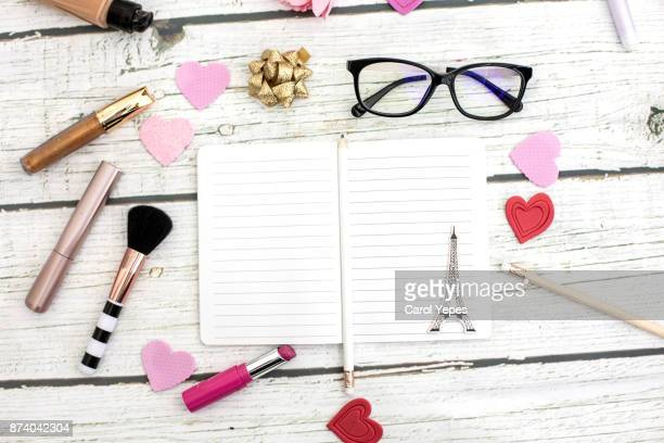top view pink notebook, beauty brushes, tulips and pink lipstick, hearth shape donut on pink ackground