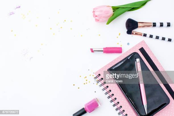 top view pink notebook, beauty brushes, tulips and pink lipstick un white background