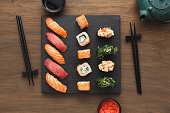 Japanese restaurant, sushi roll on black slate . Set for two persons with chopsticks, ginger, soy sauce on rustic wood background. Top view, copy space