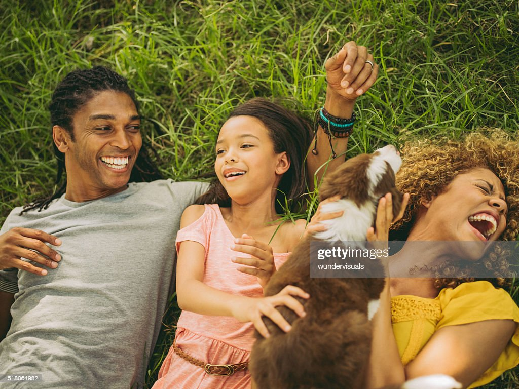 Top view shot of African-American family lying on their backs : Stock Photo