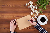 Top view woman hands writing on the blank paper sheet with blank copy space for text, white flowers and cup of coffee on wooden background