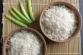 Top view: steamed cooked white basmati rice in round ceramic bowls over black stone background