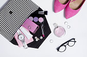Top view striped clutch with woman accessories and pink shoes . Decorative beauty makeup stuff