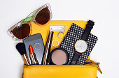 Top view trendy accessories for woman. Fashion sunglasses, yellow bag , watch , mascara , smart phone, rings