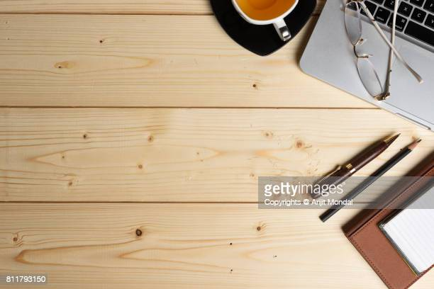 Top view wooden finish table with laptop, tea cup, pen, pencil, note book and spectacle