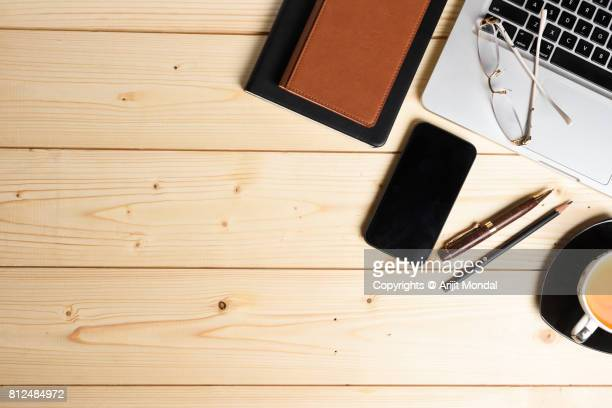 Top view wooden office desk with smartphone blank screen, office stuffs and copy space
