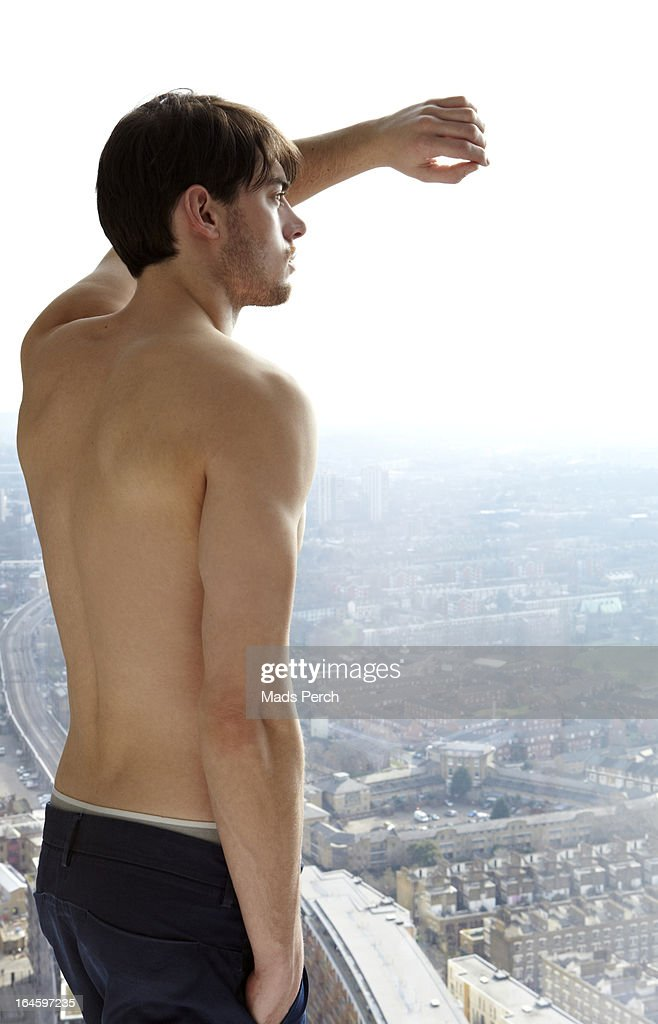 toples guy looking out on city from his flat : Stock Photo