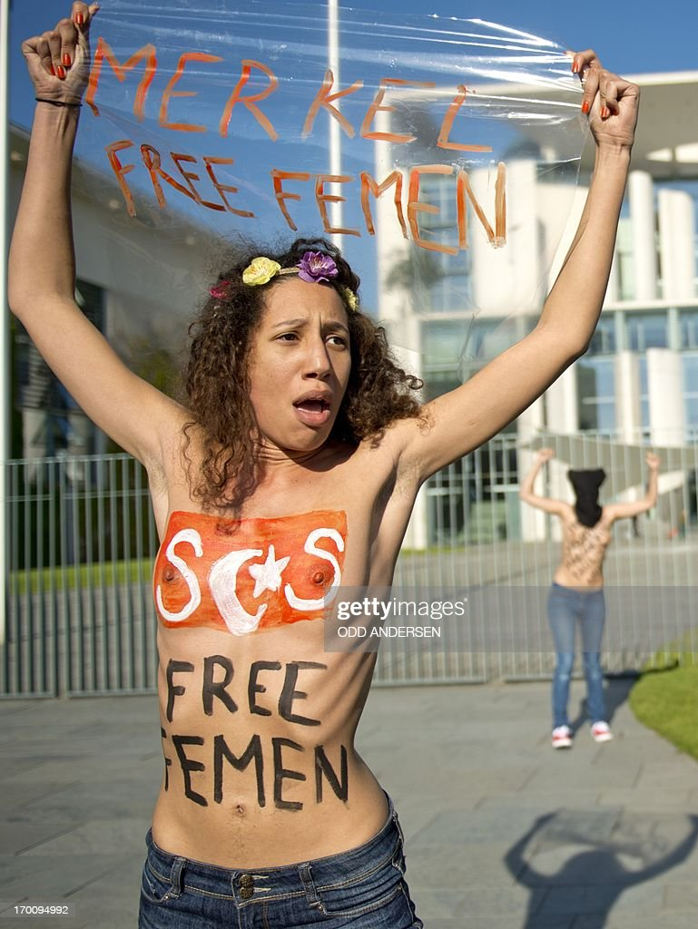 A topless activist from women's rights group Femen has 'SOS free Femen' painted on her breast as she shouts slogans outside the Chancellery in Berlin to protest against Tunisian prime Minister prior to his meeting with German Chancellor on June 7, 2013. Angela Merkel is to meet later today with Ali Larayedh. The action is held to support Amina Sboui, a young Tunisian arrested for an anti-Islamist protest inspired by topless protest group Femen. ANDERSEN