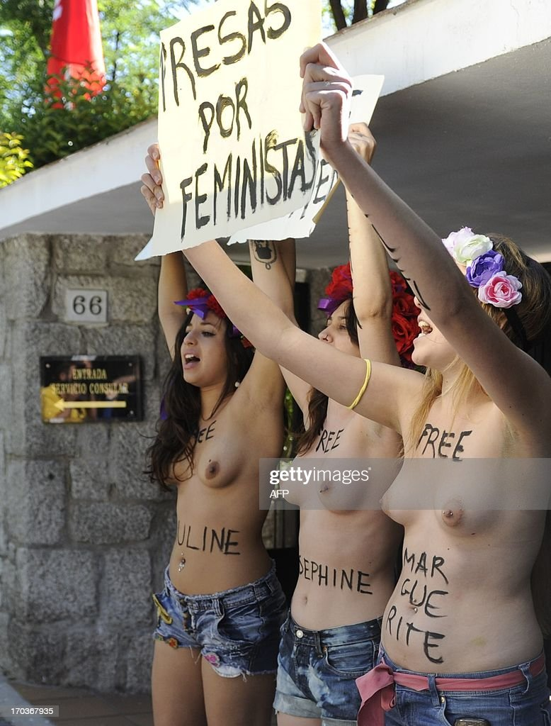 Topless activist from women's rights group Femen hold placards reading ' Free Femen' during a protest in front of the Tunisian Embassy in Madrid on June 12, 2013. The action is held to support four Femen activist, two French and one German arrested in Tunis for baring their breasts outside the main courthouse in Tunis on May 29, in solidarity with a Tunisian activist who had been arrested 10 days earlier. AFP PHOTO/ Curto de la Torre