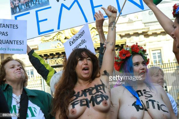 Topless Femen activists holds signs at the courthouse where Femen activists go on trial for showing their breasts during a protest at a rally against...