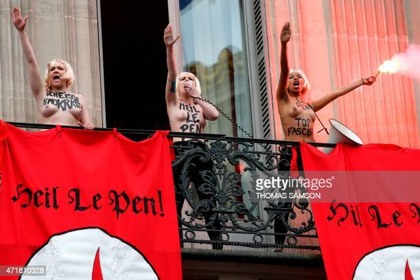 Topless Femen activists perform the Nazi salute near flags reading 'Heil Le Pen' as they demonstrate on a balcony against France's farright Front...