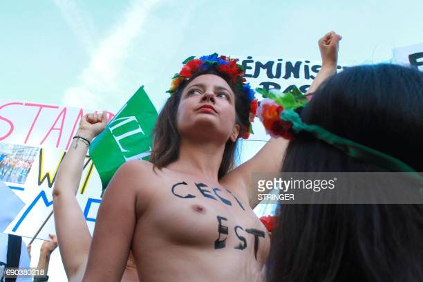 Topless Femen activists raise their fists and holds signs at the courthouse where Femen activists go on trial for showing their breasts during a...