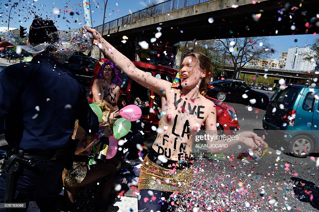 Topless Femen activists throw confetti as they protest outside a banquet held by France's far-right Front National (FN) party in honour of Jeanne d'Arc (Joan of Arc) at the Porte de La Villette in Paris on May 1, 2016. / AFP / ALAIN