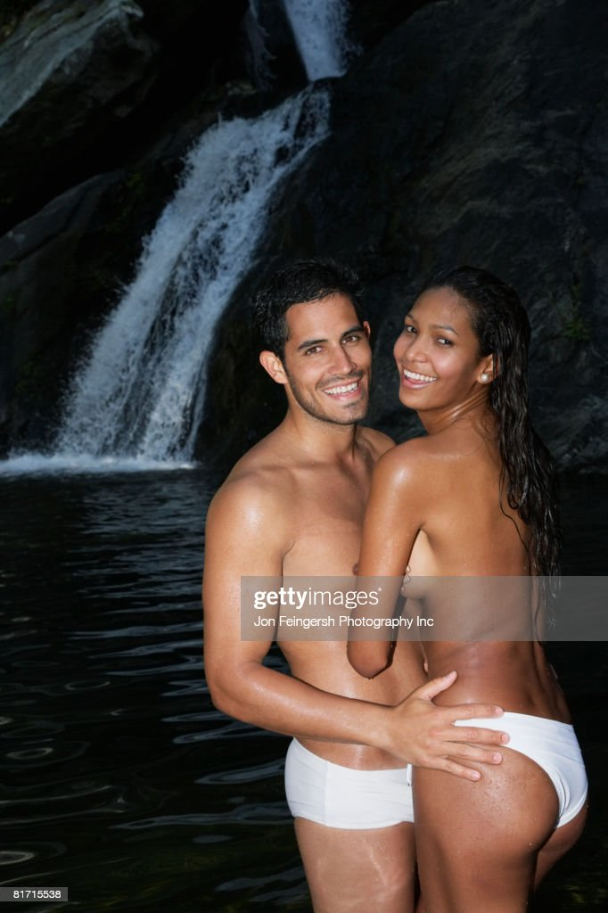 Topless Hispanic couple hugging : Stock Photo