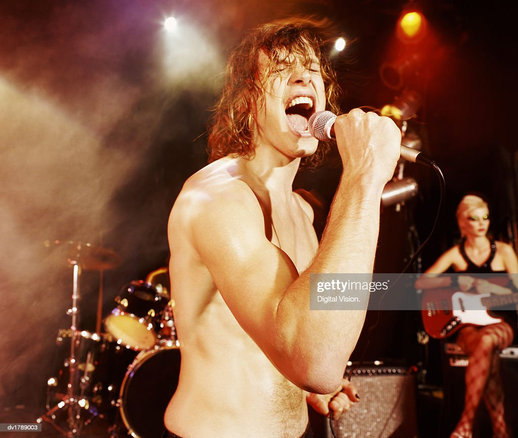 Topless Male Rock Singer Stands on a Spot lit Stage Screaming Into a Microphone : Stock Photo