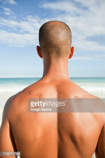 Topless man at beach, rear view : Stock Photo